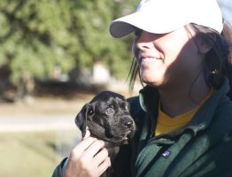 A JCJC student holding a puppy at last years Puppies on the Patio.